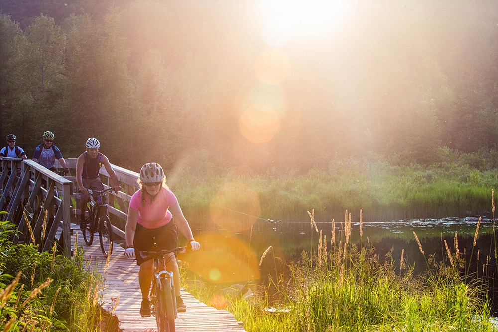 Family riding bikes together on wooden bridge