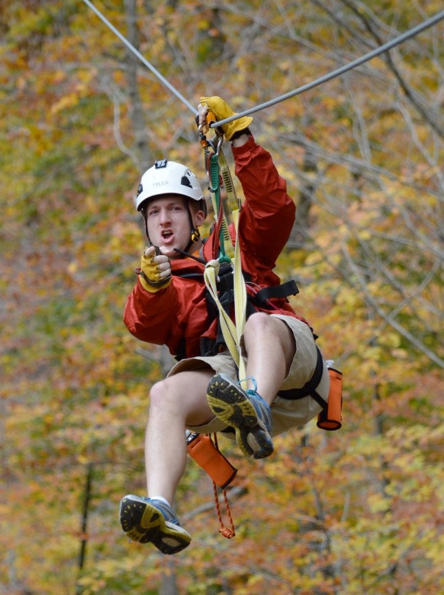 Man pointing at camera on zip line